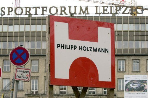Behind the logo of construction company Philipp Holzmann AG is the <i>Sportforum</i> Leipzig and the central stadium in there. Photo: DPA