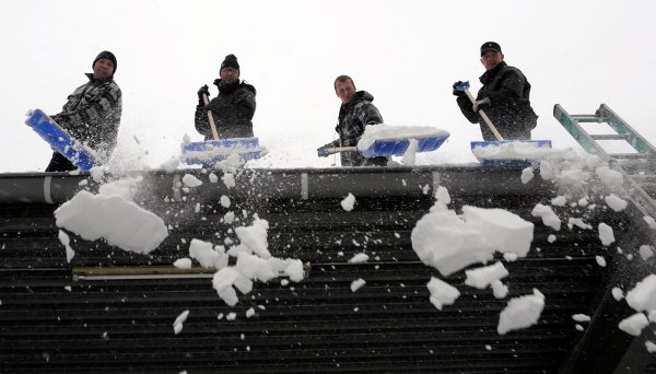 Men sweep a Lüdenscheid roof clean of snow.Photo: DPA