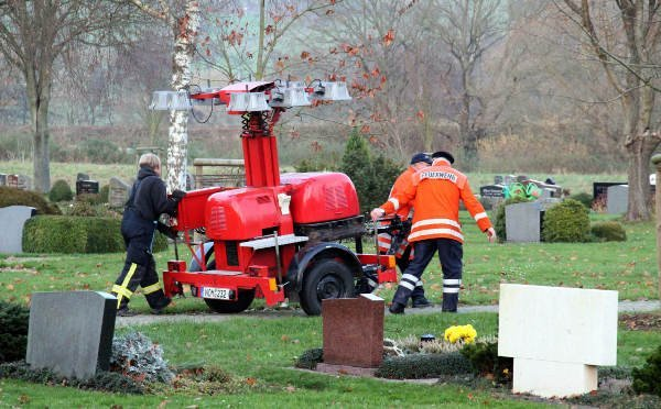 Emergency services build a lighting tower in a Bodenfelde cemetery to search the area as night draws near on Sunday.  Photo: DPA