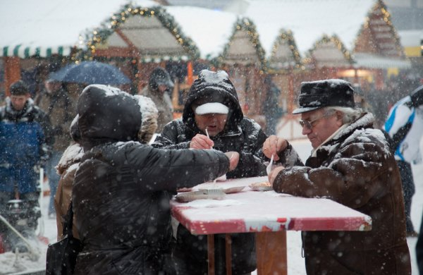 Berlin was hit by heavy snowfall over the weekend. But Christmas shoppers were undeterred. This group warm up with some traditional Berlin curried sausage at a Christmas marketPhoto: DPA