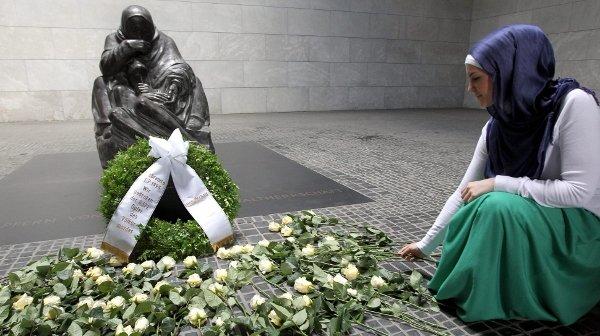 Mother and her Dead Son: the statue of a grieving woman holding the body of her dead son, created by the sculptor Käthe Kollwitz and housed in the <i>Neue Wache</i> on Berlin's Unter den Linden. The 1818 building has always been used by different governments to commemorate the dead of war, and after German reunification Kollwitz's statue was installed as an expression of that loss. Here flowers are laid to mark the Srebrenica massacre.Photo: DPA