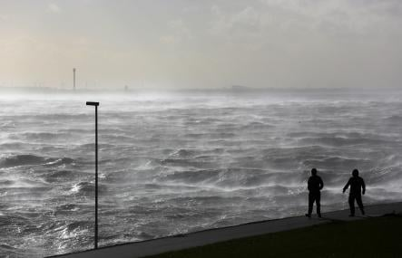 Two walkers brave the stormy waterfront at Brunsbüttel in the north west of Germany.Photo: DPA