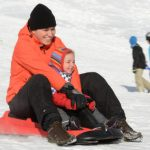 Mother and child sledging in the village of Hofsgrund in the Black Forest mountains.