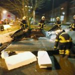 Firemen rush to a roof blown off in Rostock. Photo: dpa