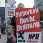 """An NPD supporter hides behind his sign, which says """"Security through law and order.""""Photo: J. Arthur White"""