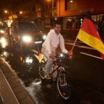 In Koblenz, a fan on a bicycle joins a motorcade to celebrate the German victory.Photo: DPA