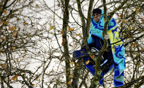 Refugee protesters escape police in trees