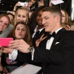 Some lucky young fans get a picture with dapper football <i>Weltmeister</i> Bastian Schweinsteiger on the red carpet. Photo: DPA