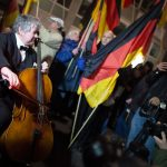 A cellist plays in front of 'Dügida' demonstrators in Düsseldorf. Some 5,000 people came out to protest against the anti-Islam movement there.Photo: DPA