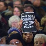 A woman holds a sign that reads 'We are Charlie, we are not Pegida' during a protest in Düsseldorf.Photo: DPA