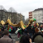 A man dressed as St. Patrick, who was known to have driven the snakes from Ireland, leads a group of people propping up a golden serpent. Photo: Emma Anderson, The Local