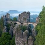 """<b>Saxon Switzerland National Park.</b> A major attraction of this Saxony park outside Dresden is the Bastei Bridge pictured here, built on a one-million-year-old rock formation that towers 194 metres above the Elbe River. The rocks make the park a popular destination especially for climbers and hikers.Photo: <a href=""""http://bit.ly/1qRgL2v"""">Thomas Wolf</a>/Wikimedia Commons."""
