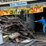 A man in Simbach am Inn, Bavaria, clears debris from in front of a shop with a snow shovel.Photo: DPA