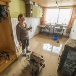 A woman in Triftern, Bavaria, wades through her ruined sewing workshop.Photo: DPA