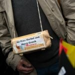 """A demonstrator has an egg-box tied around his neck, with the message: """"For Mrs. Merkel and Mr. Gauck [the German President] ten fresh free-range eggs""""Photo: DPA"""