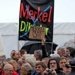 """The celebrations were also marked by demonstrations by the anti-Islam Pegida movement. Here, protesters hold up banners reading """"Merkel has to go"""" and """"Merkel Dictatorship"""", which has been crossed out.Photo: DPA"""