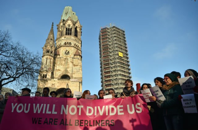 Refugees, Berliners sing together against hate at attack site