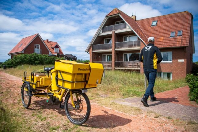 A postal worker delivers a parcel in Baltrum, Lower Saxony.