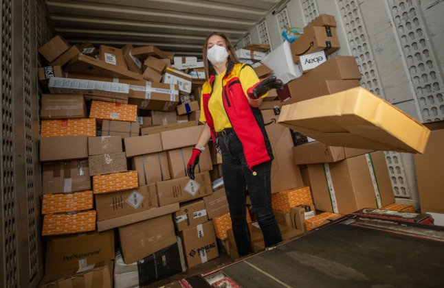 A Deutsche Post employee loads a van with parcels during a night shift.