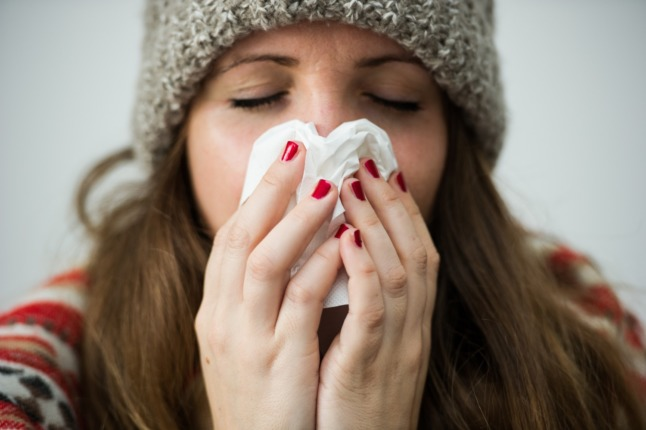 A woman sneezes into a tissue. Doctors in Germany say there's an increase in people getting common colds and other respiratory infections.