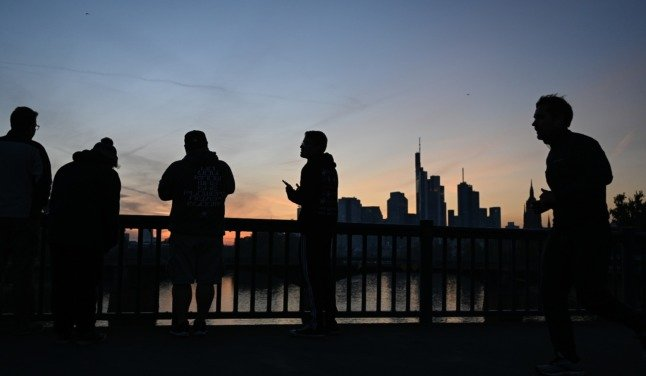 Passers-by watch the sunset in Frankfurt on October 11th.